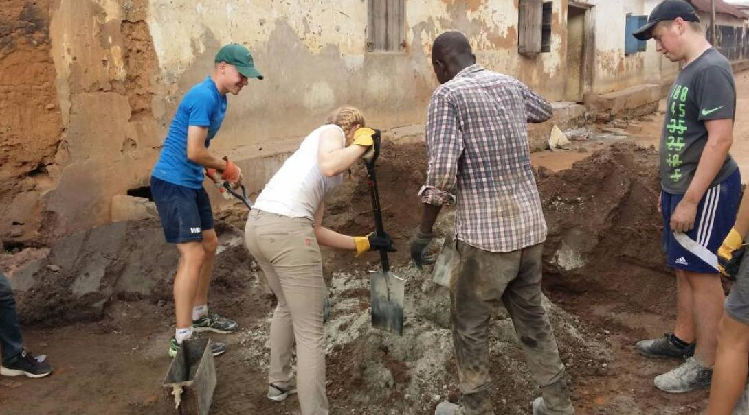 A group doing building volunteer work in Africa work with local builders to construct toilets.